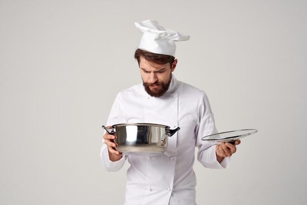 フードレストランを準備する鍋を覗き込む陽気な男性シェフ