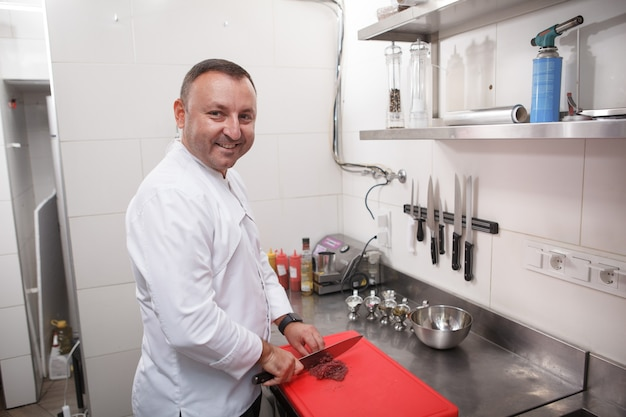 Веселый шеф-повар улыбается в камеру во время работы на своей кухне