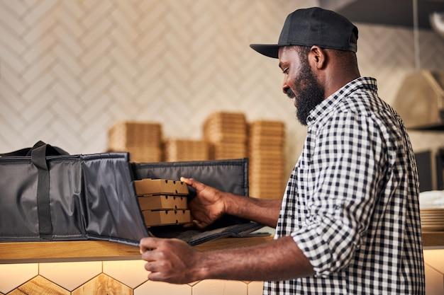 체크 무늬 셔츠에 쾌활한 남성 택배 절연 열 포장 가방에 골판지 피자 상자를 포장