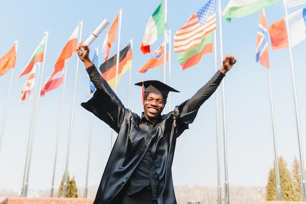 Веселый мужской танец празднует выпускной на открытом воздухе университета, знания