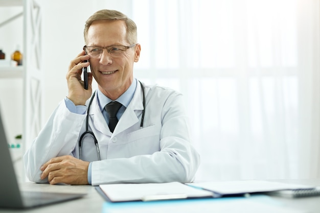 Cheerful male doctor having phone conversation in clinic