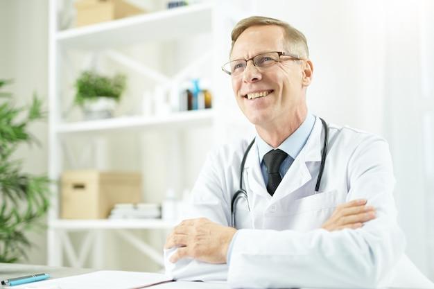 직장에서 테이블에 앉아 쾌활한 남성 의사