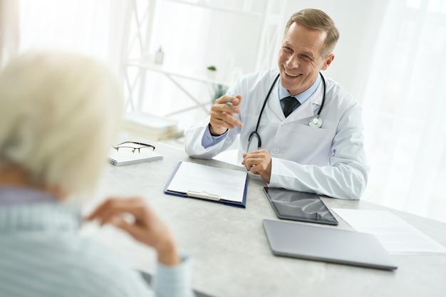 彼のオフィスで年配の女性と話している陽気な男性医師