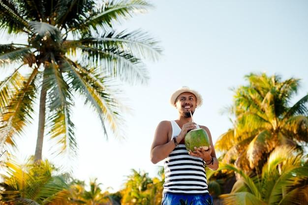Веселый мужчина пьет кокосовое молоко на тропическом пляже во время отпуска