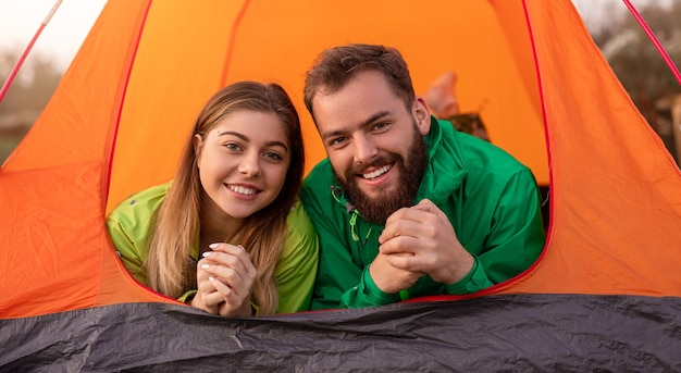 Cheerful male and female travelers smiling and looking at camera while relaxing in tent on campsite in nature