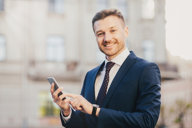 Cheerful male financier holds modern cell phone chats with partners