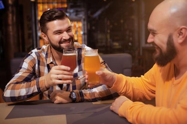 パブでビールグラスをチャリンという陽気な男性の友人