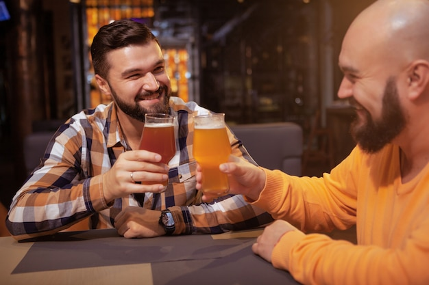 Cheerful male friends clinking their beer glasses, celebrating at the pub