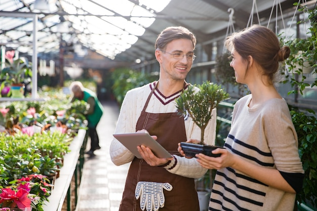 タブレットを使用し、オランジェリーの鍋に盆栽を保持している若い女性と話している陽気な男性庭師