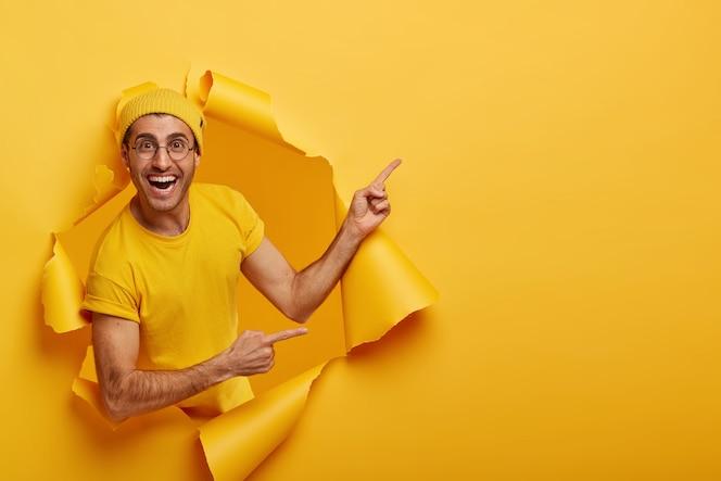 쾌활한 남성이 좋은 제안을하고, 신제품을 판매하며, 찢어진 종이 구멍에 서서, 긍정적 인 표현을합니다.