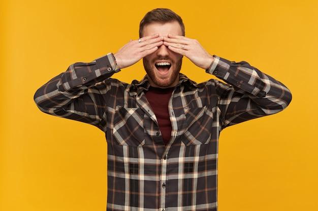 ブルネットの髪とあごひげを持つ陽気な男性、ハンサムな男。市松模様のシャツとアクセサリーを身に着けています。手のひらで目を覆い、広く笑顔で。かくれんぼ。黄色い壁の上に隔離されたスタンド