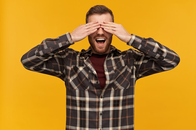 Cheerful male, handsome guy with brunette hair and beard. wearing checkered shirt and accessories. cover eyes with palms and broadly smiling. hide and seek. stand isolated over yellow wall