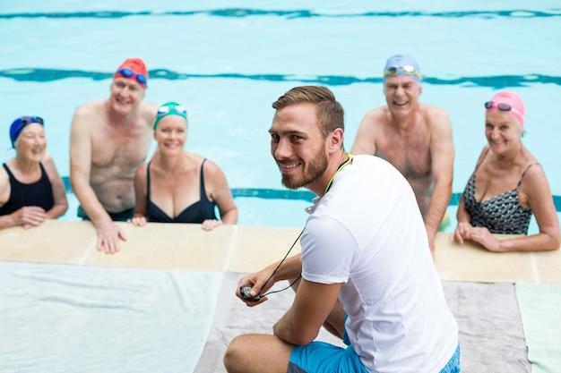 수영장에서 수석 수영을 돕는 명랑 한 남성 강사