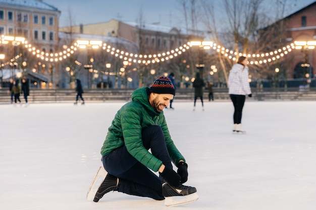 Cheerful male laces up skates as going to go skating on ice rink, prepares or puts on special shoes