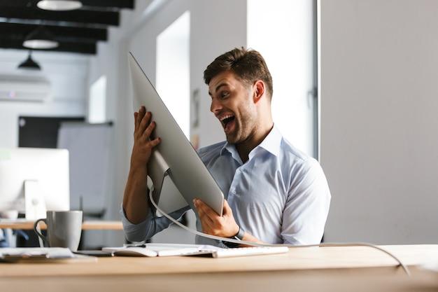 コンピューターを楽しんでいる陽気な男性マネージャー