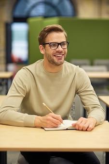 Веселый мужской офисный работник сидит за столом в коворкинге, делает заметки и улыбается