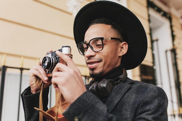 아침에 야외 작업 갈색 피부를 가진 쾌활 한 남성 사진 작가. 긍정적 인 아프리카 남자의 사진은 카메라와 함께 거리에 서있는 어두운 옷을 입는다.