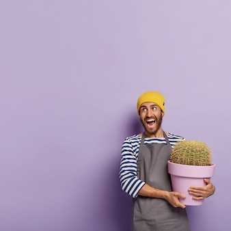 陽気な男性の植物愛好家は鉢植えのサボテンを保持し、自宅で観葉植物を気にします
