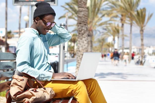 屋外でラップトップを使用して陽気な男性