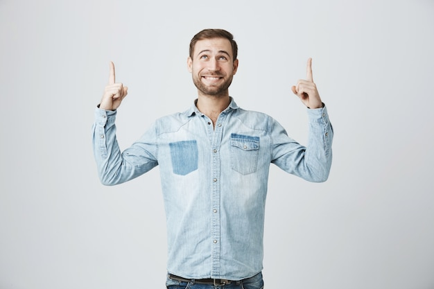 Cheerful male with beard looking and pointing up at advertisement