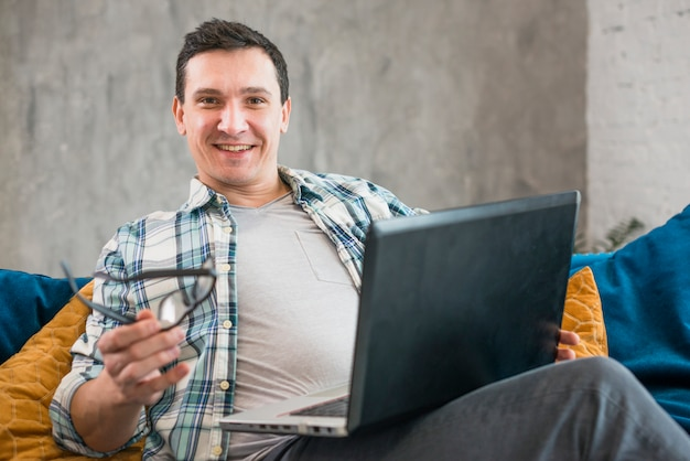 Cheerful male working on laptop at home
