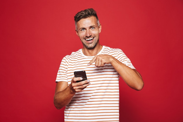 赤で隔離の携帯電話を笑顔で保持している縞模様のtシャツの陽気な男30代