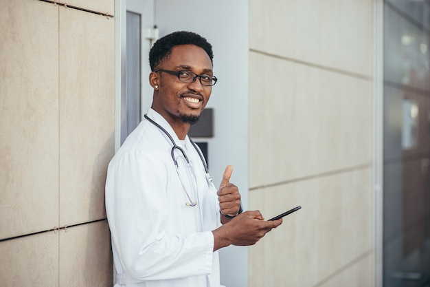 A cheerful man of an african american doctor, near the clinic, in a white medical gown looks at the camera and holds a mobile phone to talk to patients smiling at the camera reports good news