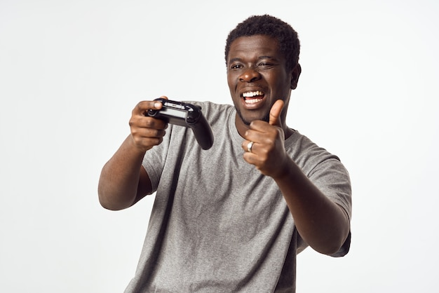 Cheerful man of african appearance with a joystick in his hands plays video games