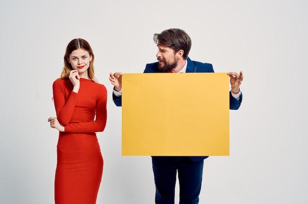 陽気な男性と女性が看板を宣伝するバナーを保持しています