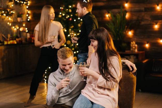 シャンパングラスを片手にお祝いの装飾が施された家で会話を楽しむ陽気な男女。お祝いのクリスマスツリーを背景に大晦日に話している若いカップル。