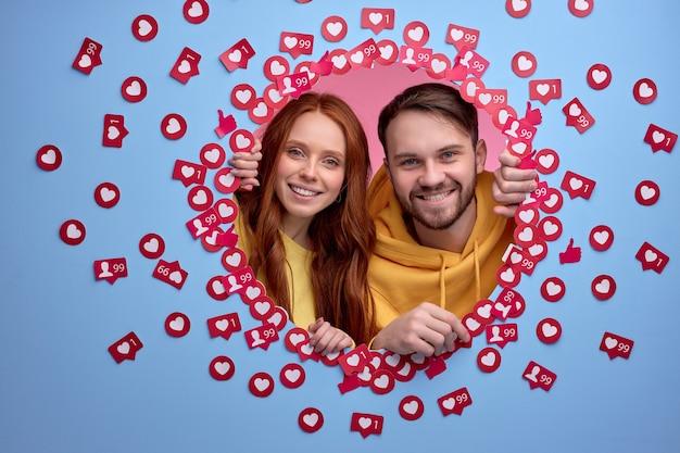 쾌활한 남자와 여자 친구가 행복하게 파란색 벽에 좋아하는 사이에 서있는 카메라를 봅니다.