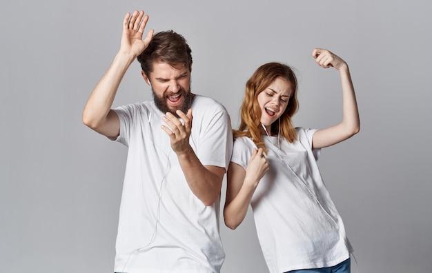 ヘッドフォンで陽気な男性と女性は灰色の背景で音楽とダンスを聴きます