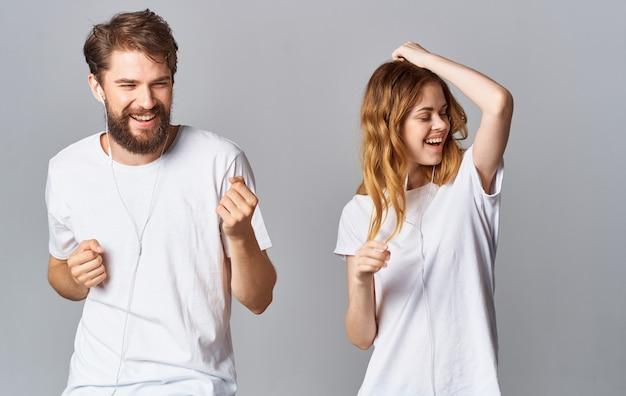 ヘッドフォンで陽気な男と女が音楽を聴き、灰色の空間で踊る
