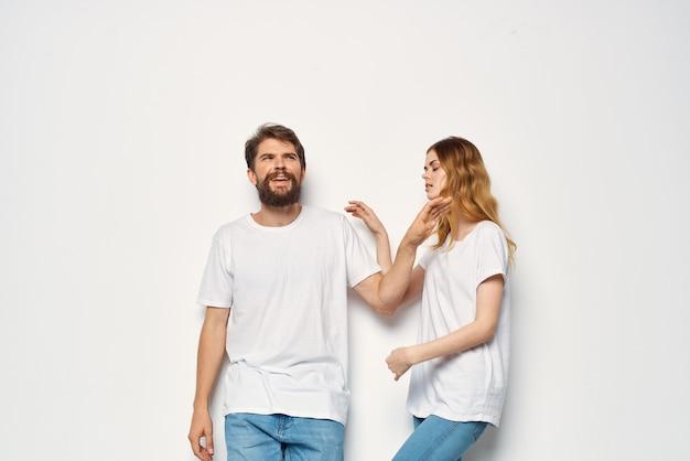 쾌활한 남자와 여자 흰색 티셔츠 스튜디오 재미 포즈