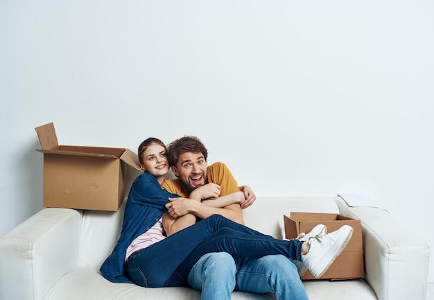 내부 골 판지 상자를 이동하는 소파에 쾌활 한 남자와 여자