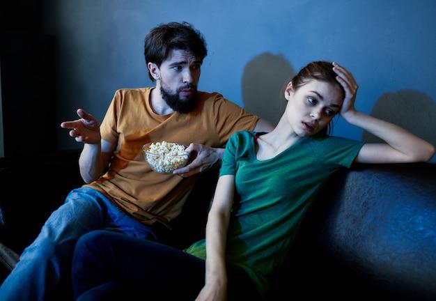 쾌활한 남자와 여자는 영화 팝콘 가족 휴가를보고 소파에 앉아