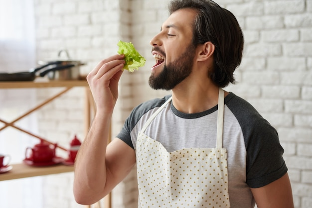 Cheerful man in apron tastes leaves of lettuce at kitchen.