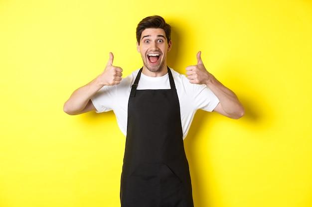 Веселый человек-бариста в черном фартуке показывает палец вверх, рекомендует кафе или ресторан, стоя