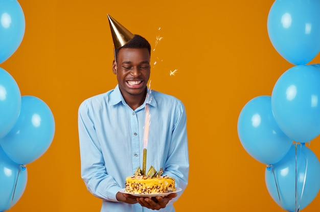 Cheerful man in cap holding birthday cake with firework. smiling male person got a surprise, event celebration, balloons decoration