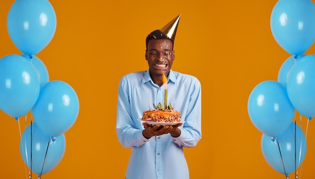 Cheerful man in cap holding birthday cake with firework, yellow background. smiling male person got a surprise, event celebration, balloons decoration