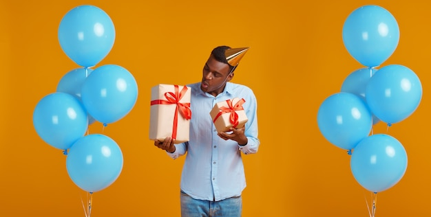 Cheerful man in cap holding two gift boxes with red ribbons, yellow background. smiling male person got a surprise, event or birthday celebration, balloons decoration