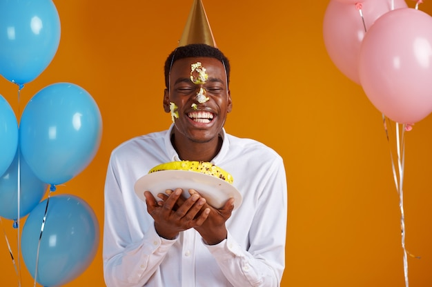 Cheerful man in cap smeared his face with birthday cake. smiling male person got a surprise, event celebration, balloons decoration