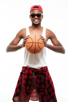 Uomo allegro in protezione ed occhiali da sole che tengono la sfera di pallacanestro