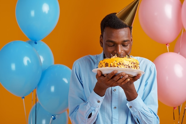 Cheerful man in cap tasting birthday cake, yellow background. smiling male person got a surprise, event celebration, balloons decoration