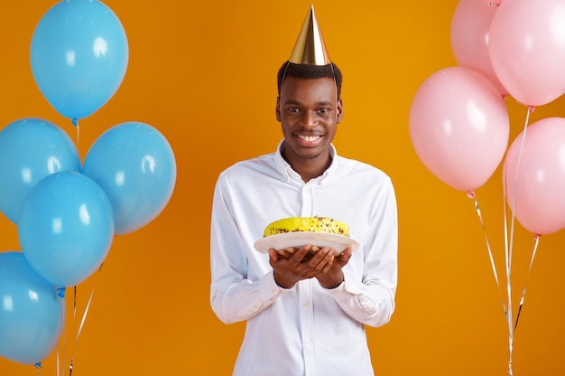 Cheerful man in cap with birthday cake, yellow background. smiling male person got a surprise, event celebration, balloons decoration
