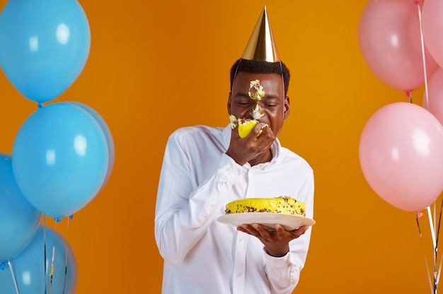 Cheerful man in cap with smeared face tasting birthday cake, yellow background. smiling male person got a surprise, event celebration, balloons decoration