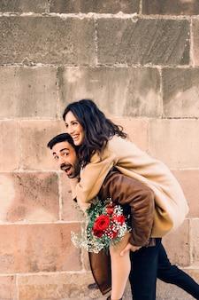 Веселый мужчина с женщиной на спине