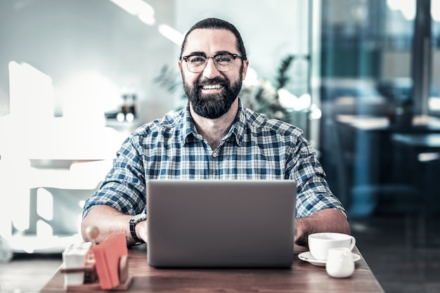 陽気な男。仕事で成功した一日の後に広く笑顔の眼鏡をかけている陽気なひげを生やした男