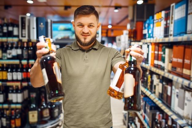Веселый человек, выбирая алкоголь в продуктовом магазине