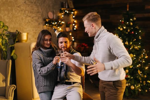 お祝いに飾られた家で大晦日パーティーを祝うカップルとシャンパングラスをチリンと鳴らす陽気な男。背景に花輪とお祝いのイルミネーションとクリスマスツリー。
